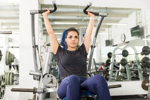 Woman in gym working out on the machines arm press