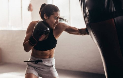 Woman hitting a punching bag in a gym in good shape boxing beginner