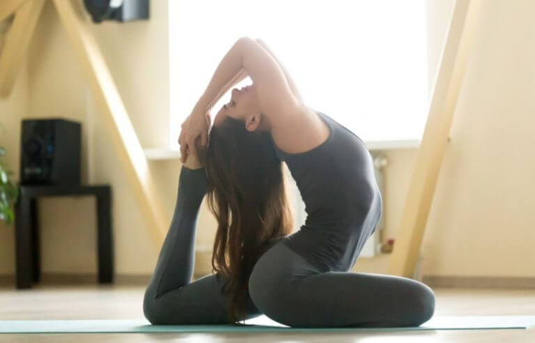 Woman in the pigeon pose for a Yogarun class