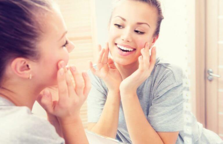 A happy woman looking in the mirror and noticing the benefits of safflower oil