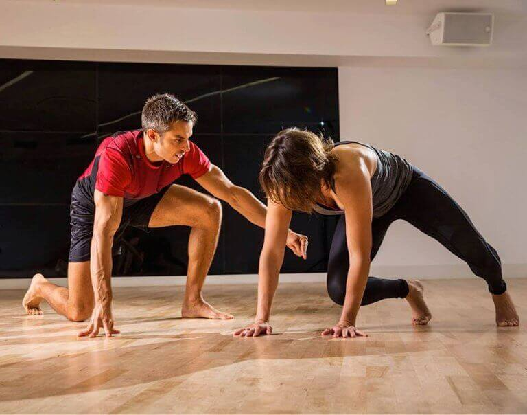 A woman performing different animal flow poses next to her trainer