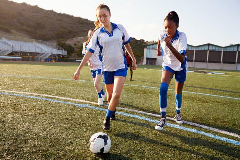 Three female football players in a field