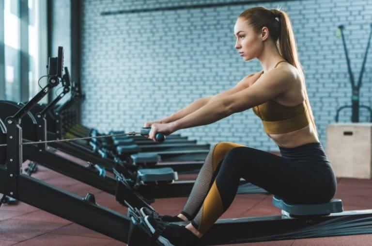 A woman using the rowing machine at the gym as part of her cardio training