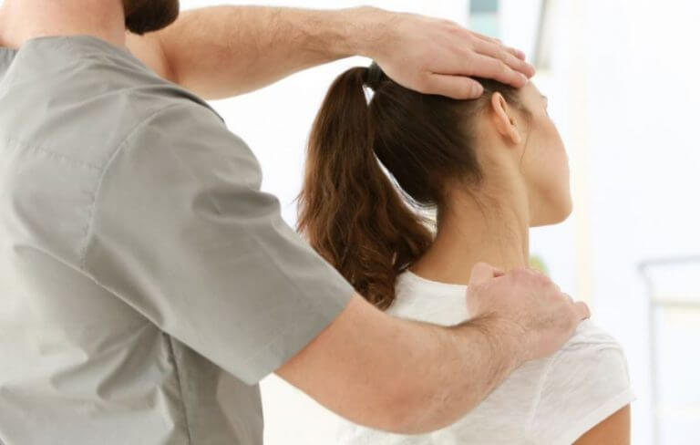 Physical therapist giving his patient a neck adjustment