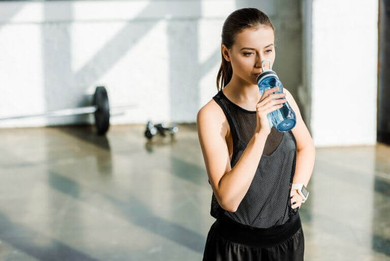 A woman drinking water to improve her physical performance