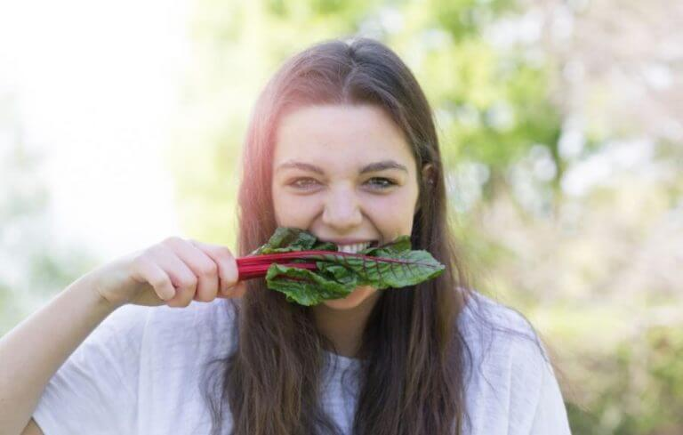 Woman biting into a dark green leaf to get enough iron