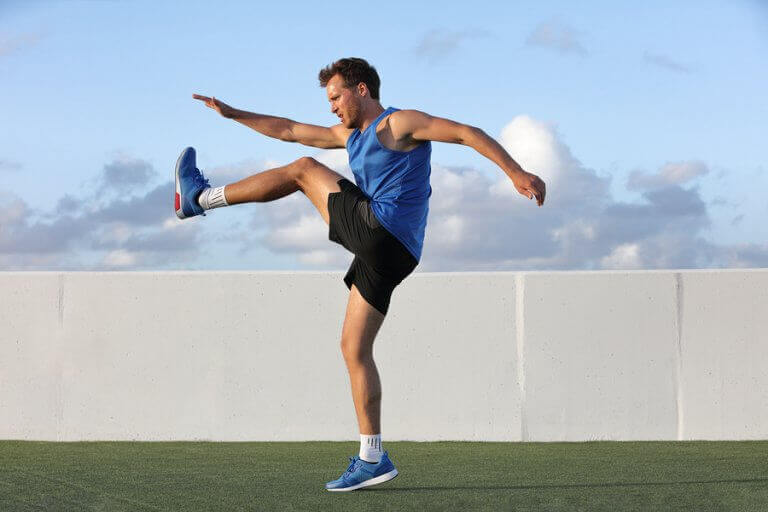 Man performing a knee raise to warm up before a training session