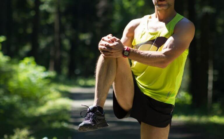 Man doing a knee raise to warm up his joints before running