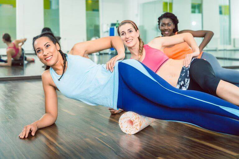 A group of women using a foam roller after their workout to alleviate muscle soreness