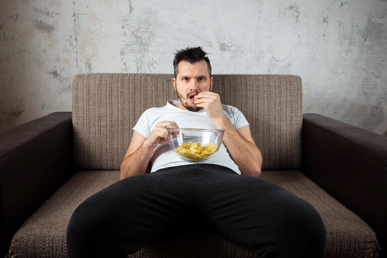 A man eating junk food while sitting on the couch to exemplify a sedentary lifestyle as one of the causes for bad cholesterol