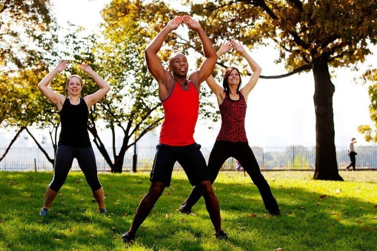 Three people doing jumping jacks in a park