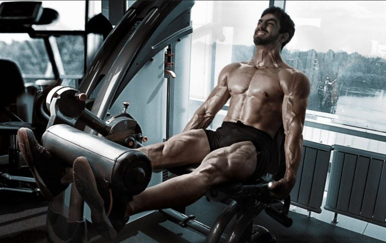 Man using a leg extension machine at the gym to strengthen his thighs