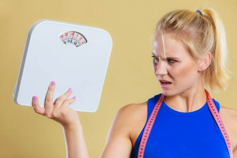 A woman holding a scale and looking at it