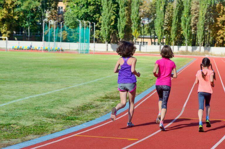 Three kids running on a synthetic track, one of the different surfaces mentioned in this article