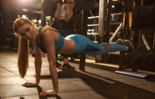 Woman doing shrugs in a plank on the gym floor