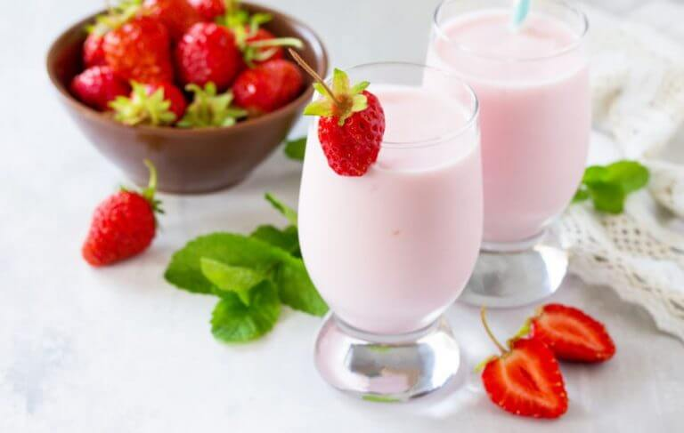Two glasses of a strawberry milkshake made using dairy products