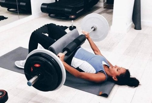 Woman at the gym using a weighted bar for a hip thrust and glute bridge