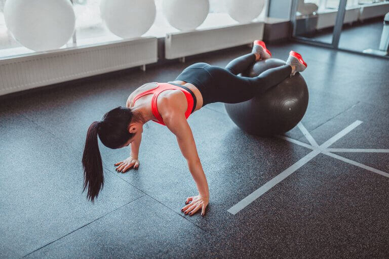 A woman doing push-ups with a fit ball