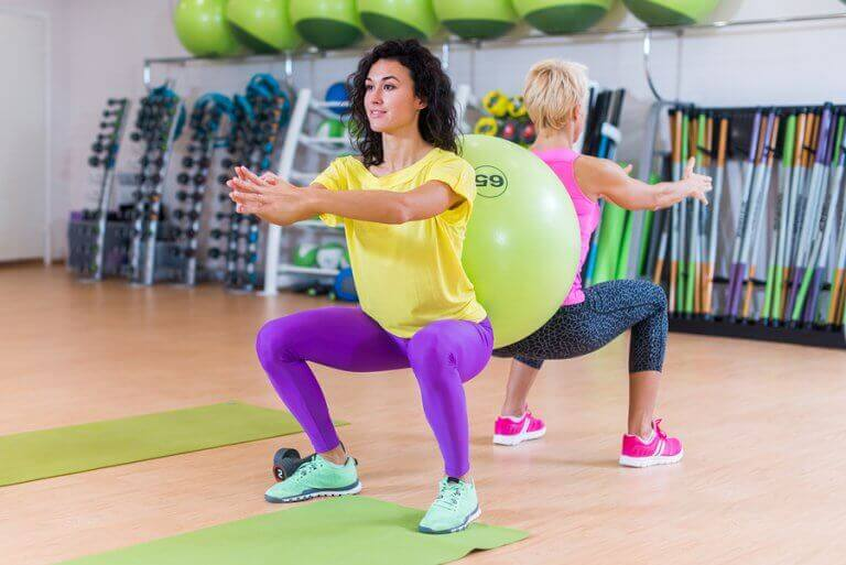 Two women doing squats with a fit ball