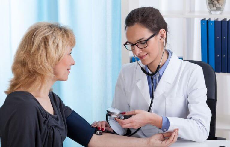 A doctor checking the blood pressure of an older woman