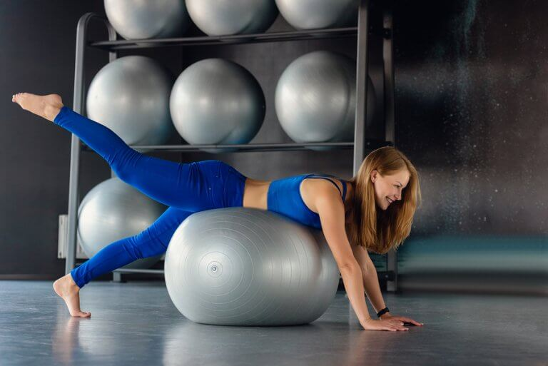 A woman doing an alternating supermar using a fit ball