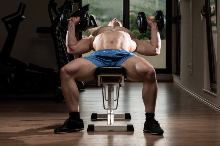 A man doing chest press exercises on an incline bench