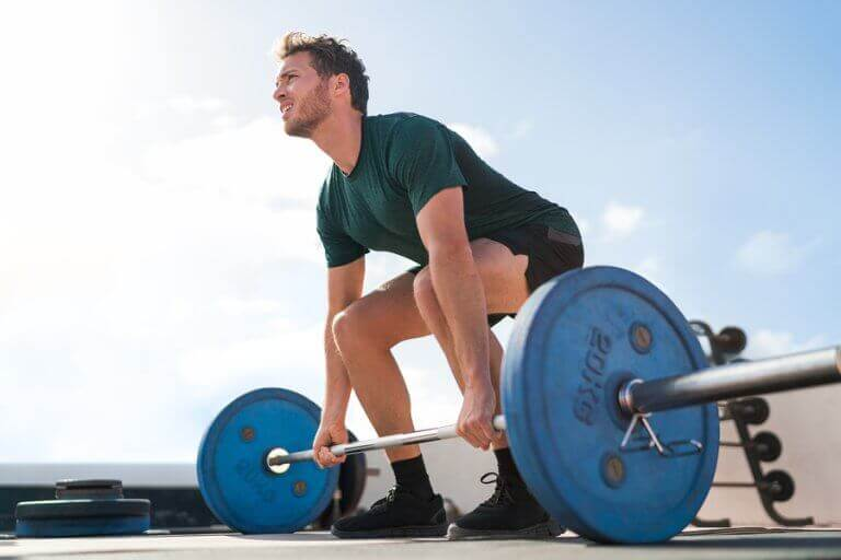 A man lifting deadweight to support the text describing this workout for back muscle strength.