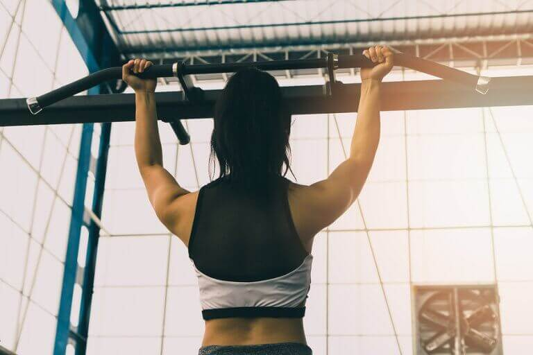 A woman doing pull ups for back muscle strength