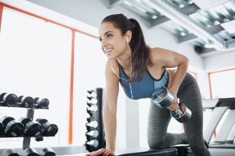 A woman on the rowing machine holding a dumbell to illustrate the description in the text