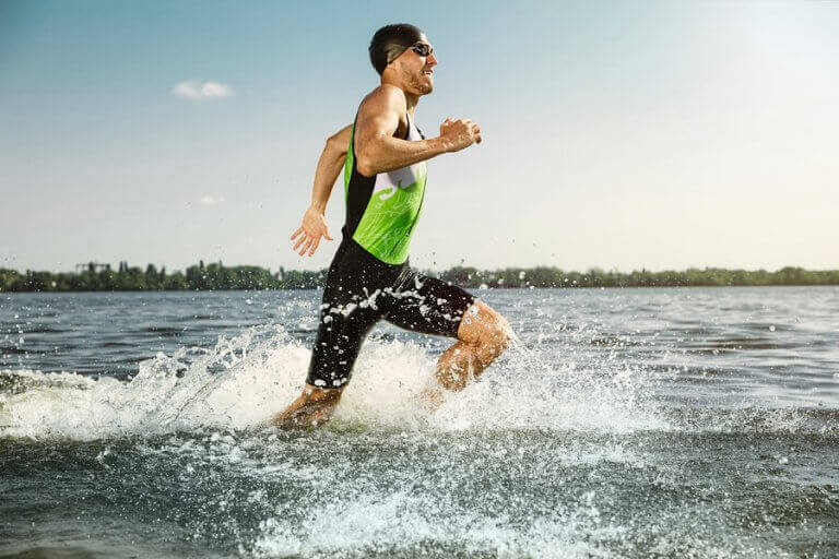A man running near the shore of the ocean