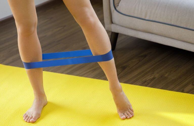 A woman using a resistance band to improve her leg workout