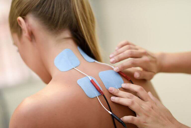 Photo of a woman having electrodes applied to her back, as described in the text to show electrotherapy benefits