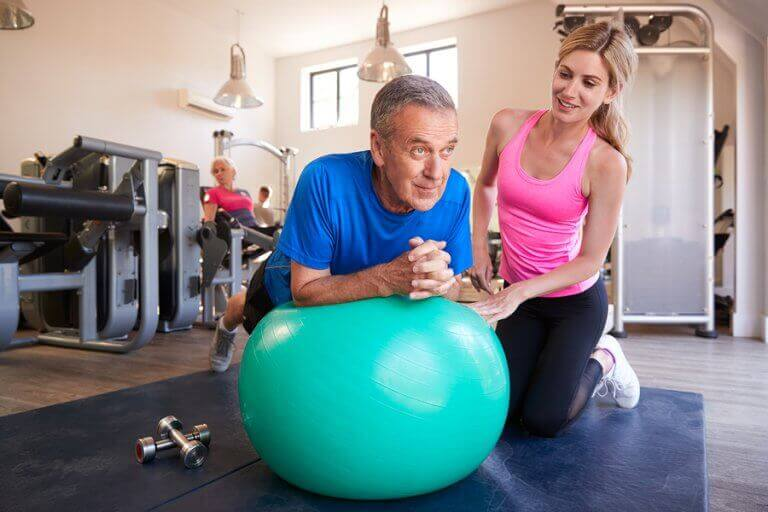 A personal trainer helping an older man to use a fit ball in his training routine