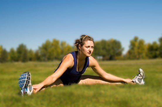 A woman doing stretches for her adductor muscles outside