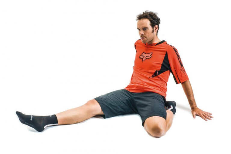 A man doing calf stretches on the floor