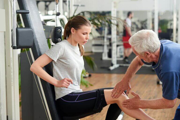 Photo of a woman getting physical therapy being assisted by a therapist.
