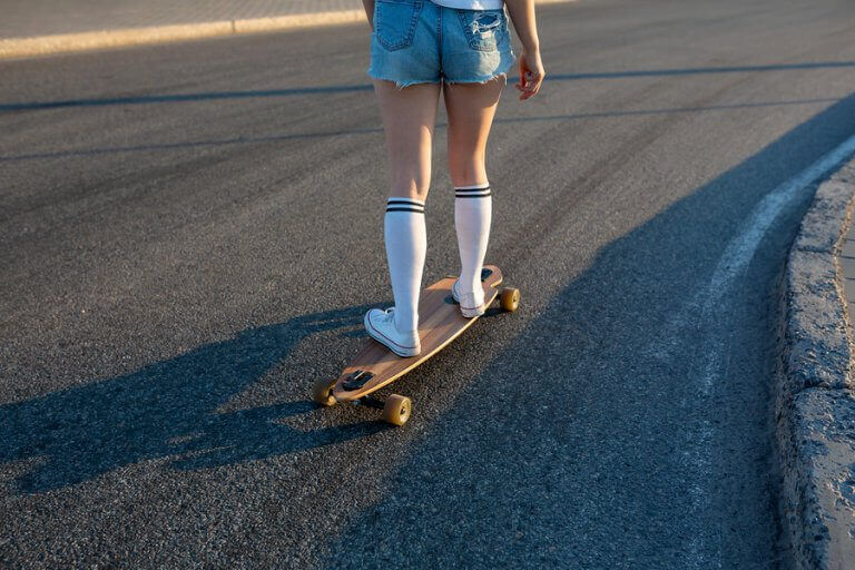 A girl riding a longboard downhill