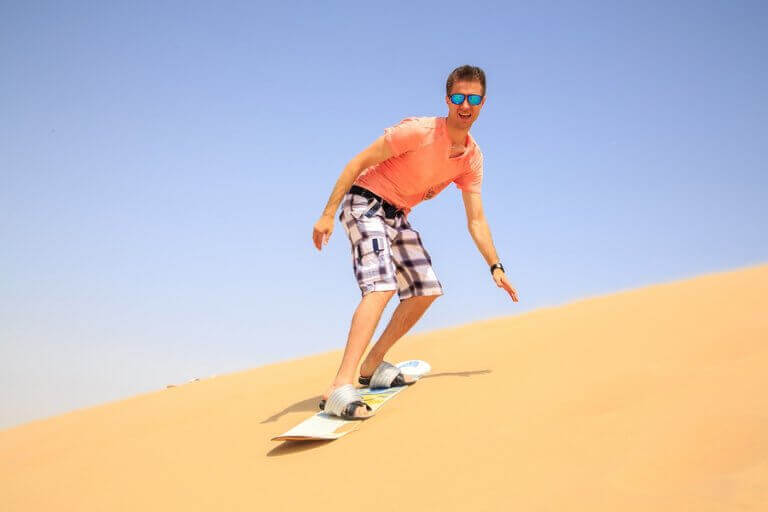 A mand sandboarding in the middle of the dessert