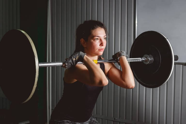 A girl lifting weights as part of her HIIT routine