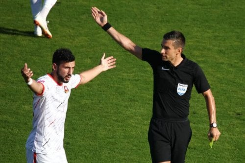 A referee explaining to a player to support the explanation in the text