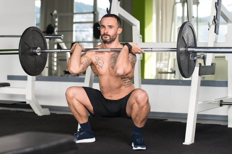 A man doign barbell squats as part of his strength training program for cycling