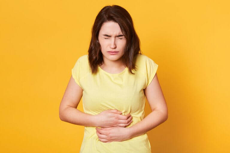 Photo of a girl holding her stomach, dealing with digestive problems.