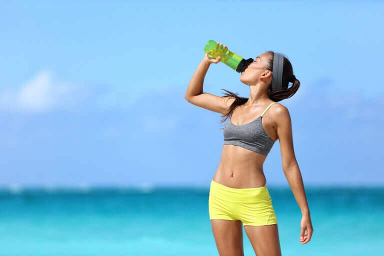 Photo of a woman drinking water to support the advice of hydrating in the text.