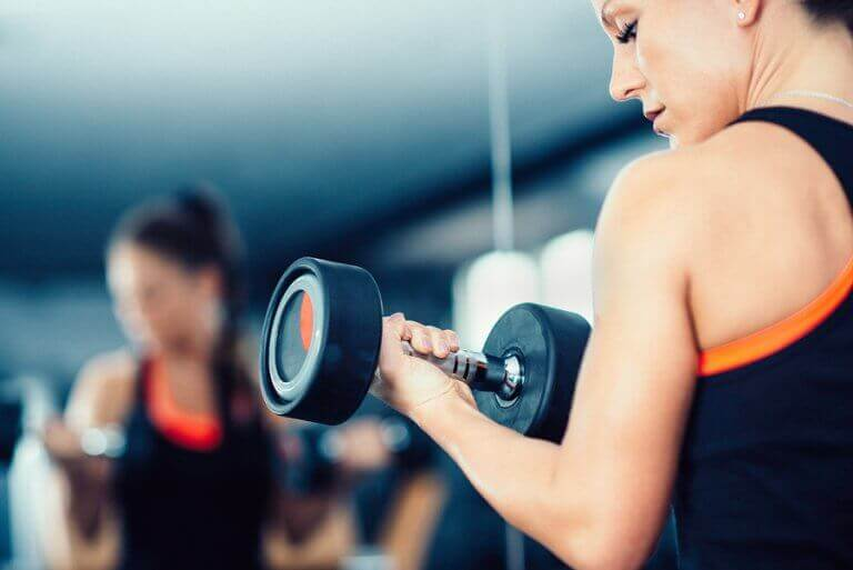 A woman lifting weights in a gym who may have vigorexia disorder