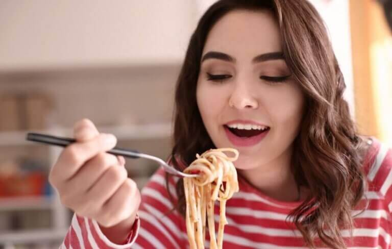 A woman eating whole wheat pasta as a carb option to gain muscle