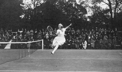 Suzzane Lenglen, playing tennis, one of the first women tennis players, supports text.