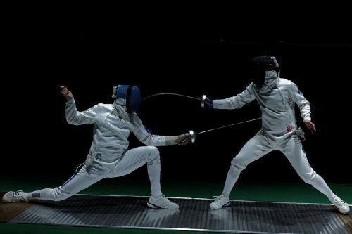 Two people engaged in a fencing match.