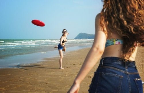 Two women throwing a frisbee around.