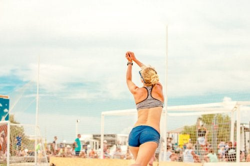 A woman playing beach volleyball which is one of the fun beach sports covered in this article.