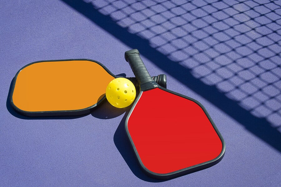 Paddles and ball on a pickleball court.